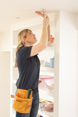 Female Electrician Installing Light Fitting In Home