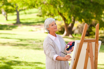 Senior woman painting in the park