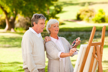 Retired couple painting in the park
