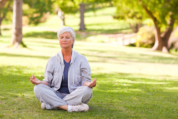 Senior woman practicing yoga in the park