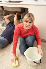 Woman Mopping Up Leaking Sink Whilst Plumber Works