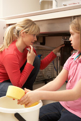 Daughter Helping Mother To Mop Up Leaking Sink