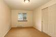 Empty white bedroom with one window and closet