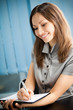Writing happy smiling businesswoman working at office