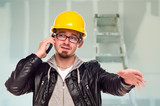 Contractor in Hard Hat on Cell Phone In Unfinished House poster