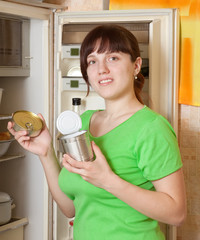 woman putting with metal can near refrigerator