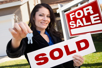 Hispanic Woman Holding Sold Real Estate Sign and Keys in Front H