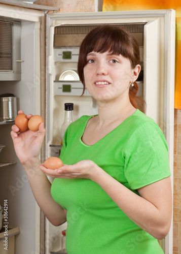 woman putting fresh eggs into refrigerator