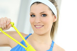 athletic woman doing gymnastic exercises with an elastic fitness poster