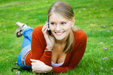 Beautiful young woman calls by mobile phone at the park