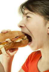 Teen girl eats a huge hamburger