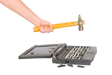 hand with a hammer destroys laptop