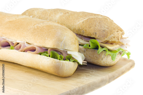 two fresh subs on cutting board