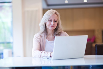 Mature woman using laptop at table