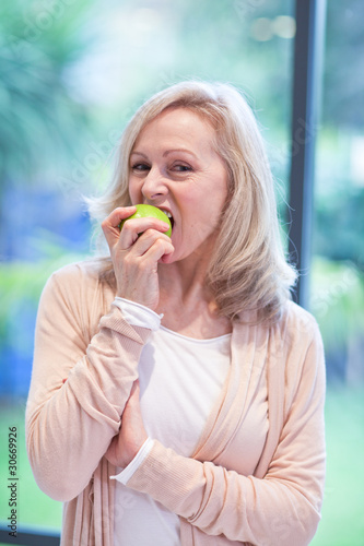 Mature woman eating an apple