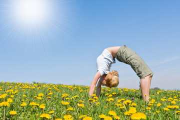 young female excercising yoga on flowery meadow