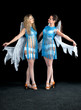 Two women in a blue dress with angel wings dance