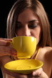 Beautiful young woman drinking cup of hot tea