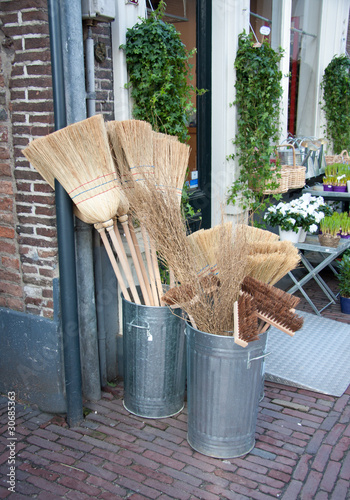 wooden brooms for sale in iron buckets in a garden center