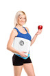 Happy young athlete holding a weight scale and an apple