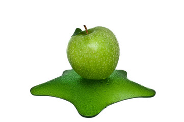 Зеленое яблоко с каплями на тарелке