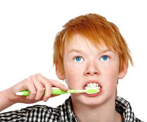 a teenage boy brushing his teeth