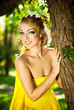 Young beautiful girl in a yellow dress in the woods