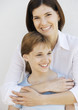 Mother with arms around preteen daughter