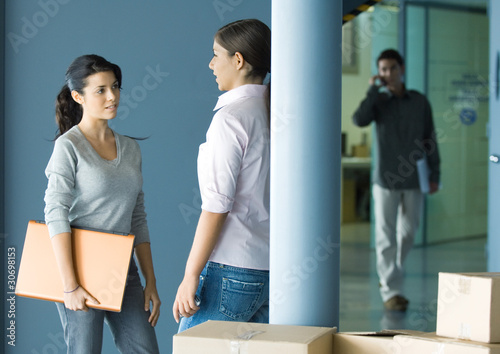 Two young women standing face to face talking, man in background using cell phone