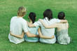 Four young friends sitting on grass, side by side, with arms around each other, rear view