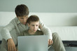 Boy and father using laptop together