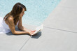 Woman lying on stomach next to pool, reading book