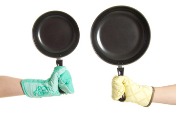 two hands in gloves holding pan's
