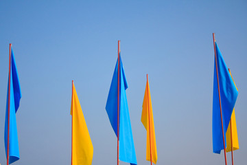 Dark blue and yellow flags on a background sky
