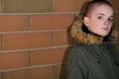 Teen Girl With Shaved Head Standing Against Brick Wall