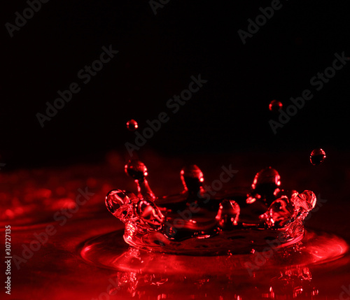 Water splash in red color with drops