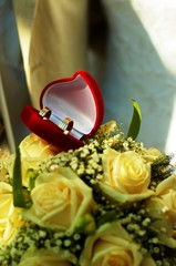 Wedding rings and yellow roses.