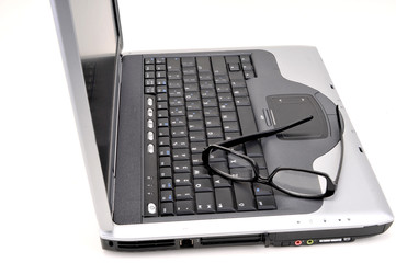 Open laptop with black glasses on keyboard