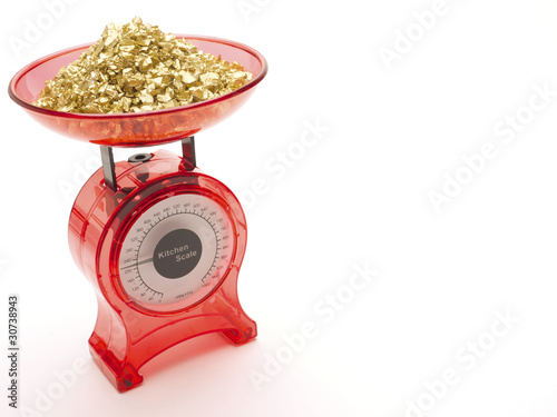 Red kitchen scales with a pile of gold being weighed