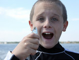 Boy holds a small fish with excitement.