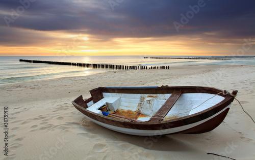 Boat on beautiful beach in sunrise