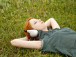 Young fashion with headphones lying at green grass