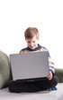 Cute young boy with laptop on couch at home