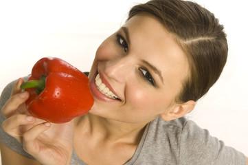 Frau beisst in rote Paprika