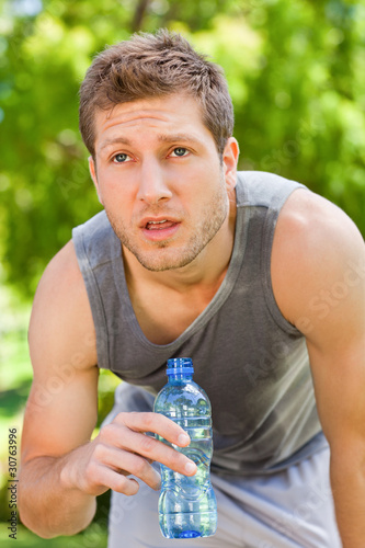Sporty man drinking water in the park