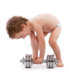 Little boy trying to lift  heavy dumbbell
