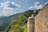 Fortress wall with Romanian flag in beautiful green environment