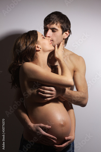Happy kissing couple embracing, woman pregnant