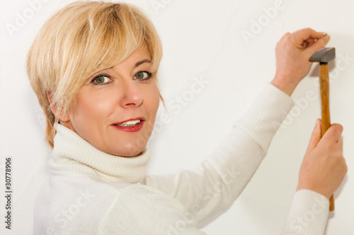 Frau schlägt einen Nagel in die Wand