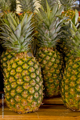 A group of pineapples on a wooden shelf